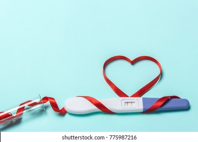 Artificial insemination, a child from a test tube, infertility treatment. Positive pregnancy test with two strips and a red ribbon in the form of a heart and a test-tube