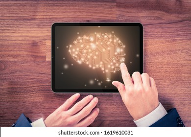 Artificial intelligence (AI), machine deep learning, data mining, and another modern computer technologies concepts. Brain representing artificial intelligence and businessman with digital tablet.