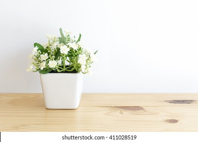 The artificial jasmine flower in the pot at the wooden table with the white wall background.