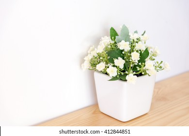 the artificial jasmine flower in the pot at the wooden table with the white wall background