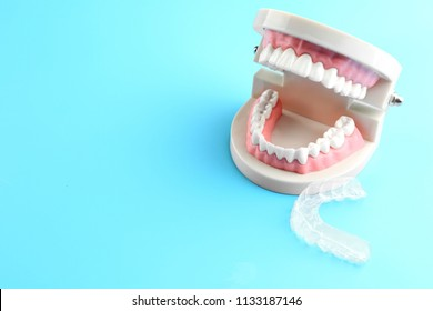 Artificial jaw and occlusal splint on color background