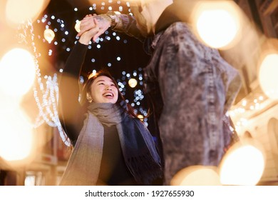 Artificial lighting by garlands. Happy multiracial couple together outdoors in the city celebrating New year.