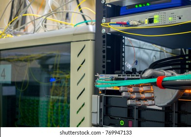 An artificial metal arm performs work in the server room. The robot switches the wires in the data center.
