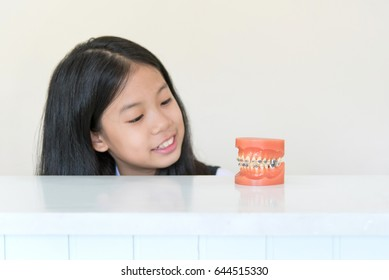 Artificial model of human jaw with dental braces in front of Asian pre teen girl with clean overbite tooth smiling in orthodontic office or clinic. Pediatric dentistry,education and prevention concept