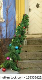 Artificial pine Christmas garland on banister outside house in Danish village