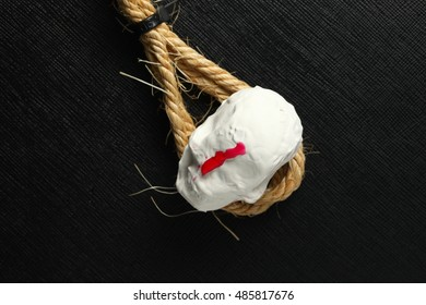 The artificial plaster miniature toy skull and red color liquid put on the manila rope.