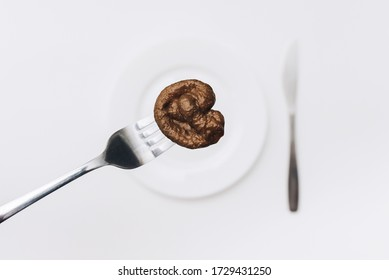 An artificial plastic feces of a cat lie on a fork near white plate and knife close-up. The concept of an fake news, inept cook, a crappy restaurant and bad food. Bad smelling joke, a taste of shit.