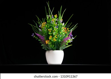Artificial potted flowers on black background.