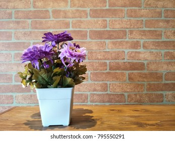 Artificial purple flowers bouquet in a white square vase place on brown wooden table with brick wall background