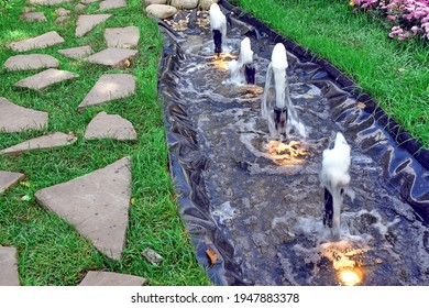 Artificial PVC Pond in Garden with Lanterns and Fountains. Small Decorative Pond or Brook in Designed Garden. Water Surface Made from PVC on Backyard.
