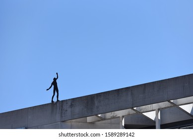Artificial silhouette of a man against the background of a blue sky that dangerously stands on the edge of a building balancing. Text space. The concept of risk and something dangerous