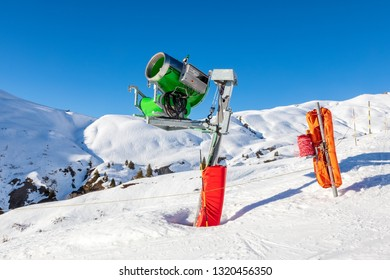 Artificial snow making machine in the Alps.  The green artificial snow gun is against a deep blue sky