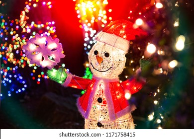 artificial snowman and snowflakes outside. smiling snowman under a decorated Christmas tree in the square. Christmas decorations