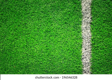 Artificial soccer grass field detail with white goal line. Vintage filter effect used.