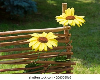 Artificial sunflowers on the decorative fence. Bright sunlight. Blurred background of green grass and trees.Ukrainian national motives.