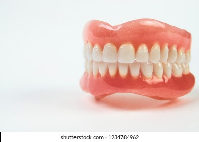 Artificial teeth on a white background with copy space. Full denture dentures close-up.