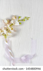 An artificial textile sprig of orchid with the green stem wrapped by two silk ribbons lays on a light gray wooden background. Top view, copy space.