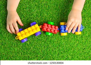 Artificial turf. Baby plays with a building kit train on a green artificial grass. Kindergarten background.