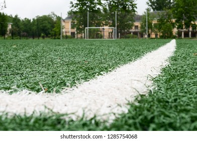 Artificial turf for football game, white line is on corner on foreground, nobody