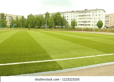 Artificial turf on the football field. Soccer field at the school stadium in the city. Background.