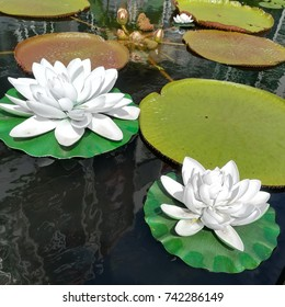 Artificial white lotus flowers from recycled plastic float amongst real plant in a pond