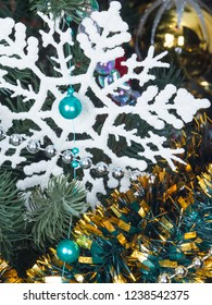 artificial white snowflake and blue and silver shiny beads to decorate the Christmas tree and gold tinsel