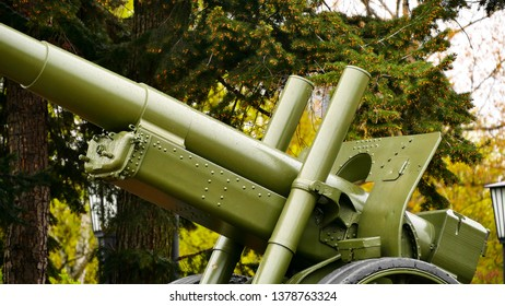 Artillery gun. Soviet (USSR) cannons from the World War II age. Sunny day in the park on a pedestal. Close up. Green russian artillery field cannon gun. Raindrops on a weapon.