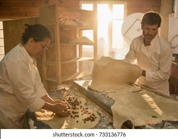 In an artisan bakery, a baker and his wife prepare the bread dough. The morning sun comes in through the window