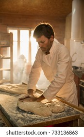 in an artisan bakery, the baker kneads the dough for the bread. The morning sun comes in through the window