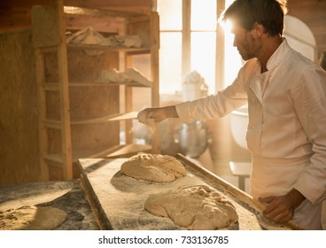 In an artisan bakery, a baker prepare the bread dough. The morning sun comes in through the window