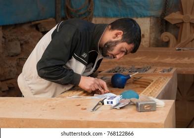 Artisan carving Armenian khachkar, Yerevan, Armenia, October 2012: A young Armenian artisan carves an Armenian cross stone at his workshop in Yerevan.