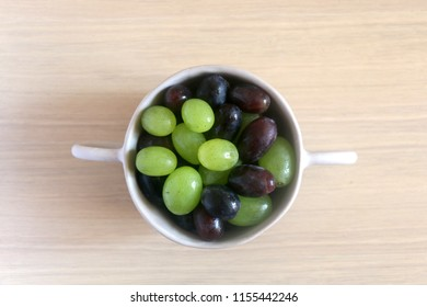 Artisan ceramic bowl filled with various types of grapes. Top view.