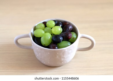 Artisan ceramic bowl filled with various types of grapes. Selective focus.