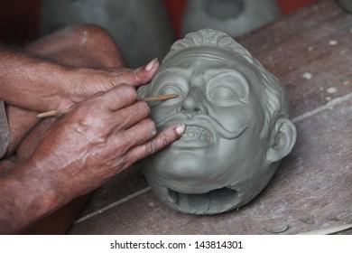 An artisan creates the head of a God for Durga Puja Festival at Kumartuli, Kolkata, India.