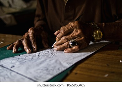 An artisan drawing pattern of flowers on a white paper, to be transferred to colourful paper and used on a traditional kites called Wau Bulan in Kelantan, Malaysia.