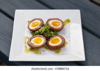 Artisan eggs in sausage shells on a white plate with garnish on a patio table of a restaurant.