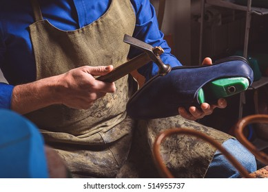 artisan holding a boot and hammer