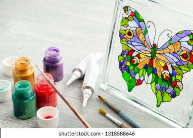 Artisan painting with stained glass paints on the glass surface.