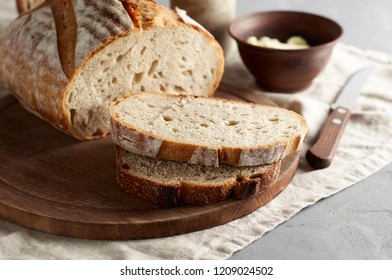 Artisan sliced toast bread with butter and sugar on wooden cutting board. Simple breakfast on grey concrete background. Closeup view