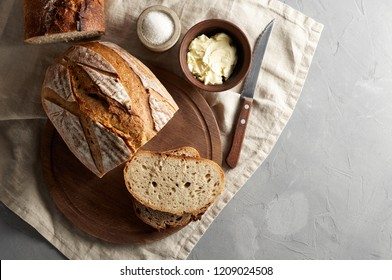 Artisan sliced toast bread with butter and sugar on wooden cutting board. Simple breakfast on grey concrete background. Top view with copy space