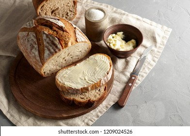 Artisan sliced toast bread with butter and sugar on wooden cutting board. Simple breakfast on grey concrete background. Top view