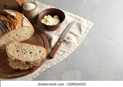 Artisan sliced toast bread with butter and sugar on wooden cutting board. Simple breakfast on grey concrete background with copy space
