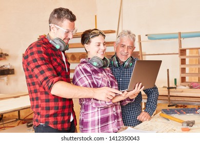 Artisan team with apprentice at laptop computer while designing a website