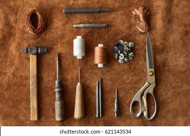 Artisan tools for working with leather: hammer, scissors, thick thread, metal wire, awl, buttons top view on leather background