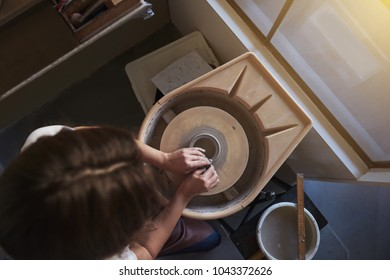 Artisan using her hands to shape a wet piece of clay turning on a pottery wheel while sitting in her ceramic workshop