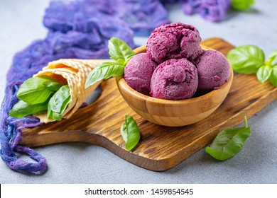Artisanal blueberry ice cream and green basil in a wooden bowl on a serving board, selective focus.