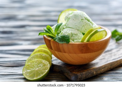 Artisanal ice cream Mojito and lime slices and fresh mint in bowl on an old wooden table, selective focus.