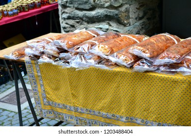 Artisanal pastry plum cakes on yellow stand at Middle autumn fair in Aosta Valley (Antey saint André). Italian typical bakery specialty. Italian food stand outdoor. Autumn holydays.