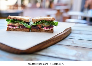 Artisanal sandwich with assorted organic vegetables cut in half and resting  on a wooden table at a sidewalk cafe