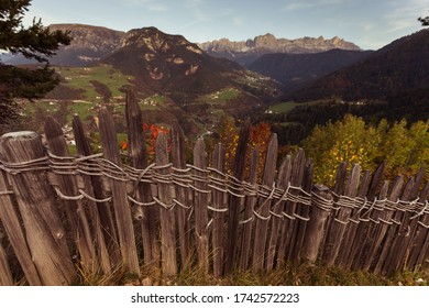 Artisanal wooden fence with Tires Valley and Catinaccio dolomite peaks in the background, Italy. Concept: autumnal Dolomite landscapes